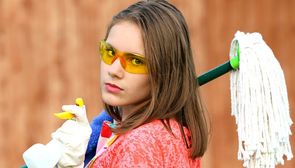 Girl with glasses holding a mop and spray bottle for house cleaning