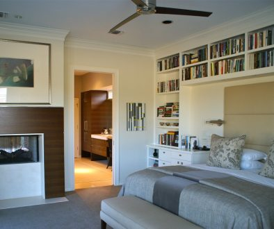 bedroom-storage-ideas-with-mid-century-modern-shelving-and-ceiling-fan-in-contemporary-bedroom-with-bed-linens-and-decorative-pill